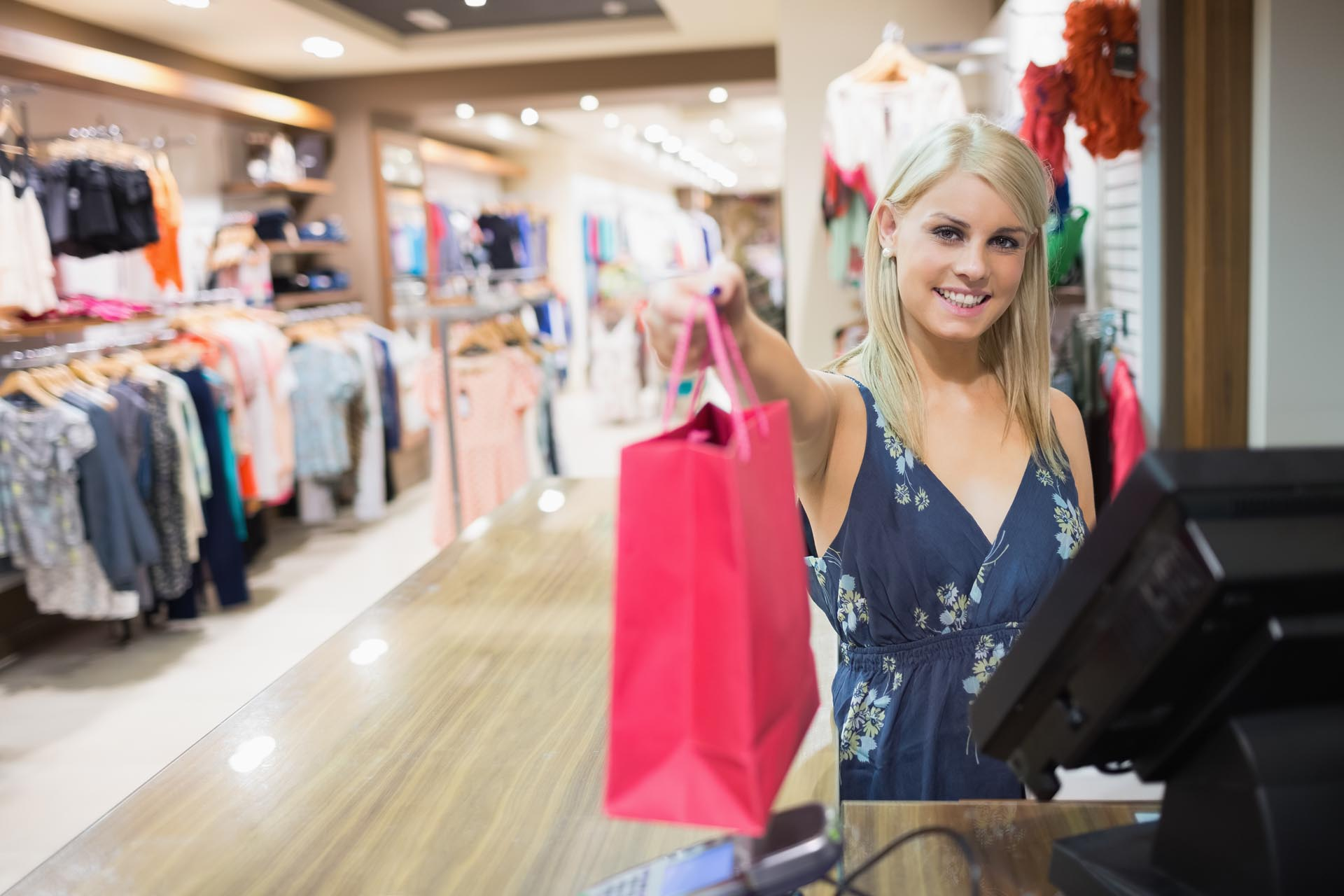 Smiling woman holding shopping bag at counter in clothes store